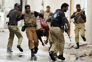 Pakistani commandos carry an injured worshipper from one of two mosques stormed by gunmen in Lahore