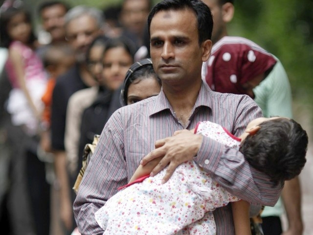 A Pakistani refugee who is a member of the Ahmadiyya, an Islamic minority sect, carries his daughter as he is released from a detention centre in Bangkok June 6, 2011. PHOTO: REUTERS/ FILE
