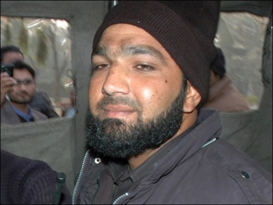 Arrested Qadri sits in a police van at the site of a fatal attack on Salman Taseer, the governor of Punjab, by his bodyguard in Islamabad on January 4, 2011. PHOTO: AFP
