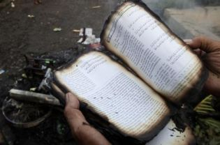 A follower of the minority Islamic sect, Ahmadiyah, holding a burnt copy of the Koran in Ciampea, West Java, after violence directed at the Islamic sect earlier this month. In what is likely to be a hugely controversial - if not illegal - decision, authorities in West Nusa Tenggar plan to relocated 20 sect families to a deserted island in Lombok. (Reuters Photo/Dadang Tri)