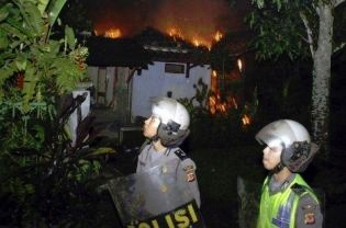 Anti-riot police walking in front of a burning home belonging to an Ahmadiyah follower in Ciampea, West Java, in October. 2010 was rife with examples of hard-line Islamic groups repressing minority groups by denying permission to build houses of worship, sometimes with the backing of government officials. (Reuters Photo)