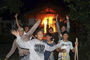 Youths chanting in front of a burning house belonging to an Ahmadiyah follower in Ciampea, West Java, late last year. A total of 216 cases of violations of religious freedom across Indonesia were recorded in 2010, up just a little from the 200 cases recorded in 2009, a human rights watchdog says. (Reuters Photo)