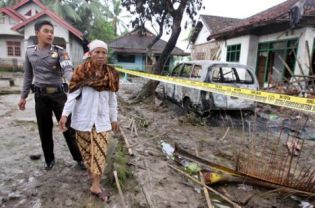 Aminah has a police guard as she surveys the house where her son was killed on Sunday. (AFP Photo/Nurani Nuutong)