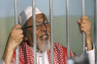 Firebrand cleric Abu Bakar Bashir talks to journalists inside a temporary cell at the South Jakarta District Court before his trial reconvened on Feb 24