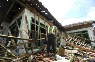 A police officer stand guards at the damaged house of a member of Ahmadiyah after it was mob-attacked in Pandeglang, Banten province, Indonesia, Monday, Feb. 7, 2011. (AP Photo)