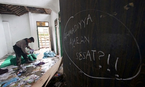 A policeman collects evidence from a house where Ahmadiyah members were attacked. The graffiti on the wall translates to 'Ahmadiyah is a devient teaching'. Photograph: Nurani Nuutong/AFP/Getty Images