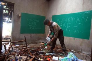 A policeman inspecting the damaged house of Ahmadiyah elder Ismail Suparman after it was attacked by a mob. The walls were daubed with graffiti in Sundanese referring to local Ahmadiyah cleric Ismail Suparman and reading 'Suparman is the Devil' and 'Suparman Die!' (AFP Photo)