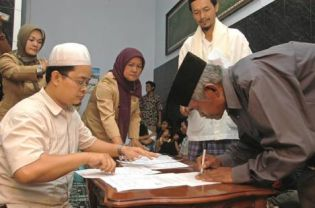 A member of the Ahmadiyah community in Ciaruteun Udik signs a document stating Islam's declaration of faith as proof of having renounced his unorthodox beliefs after attacks and calls to convert. (Antara Photo)