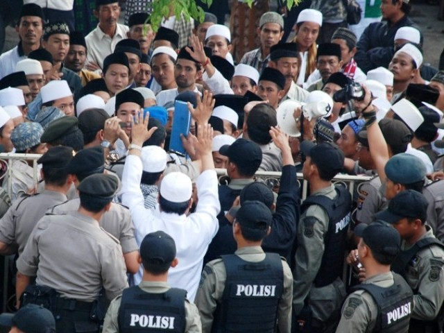 Indonesia policemen block Muslim supporters who are rallying in support for their friend, who was accused of assault on a Ahmadiyah follower, in Serang, Indonesia's Banten province July 28, 2011. PHOTO: REUTERS/FILE
