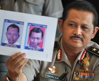 National Police spokesman Anton Bachrul Alam holds up photographs of Ahmad Yosepa Hayat, the Bethel Injil Church bomber, during a press conference in Jakarta on September 27, 2011.