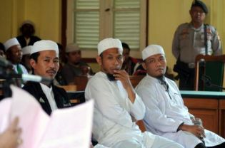 Abdurrahman Assagaf, left, head of the Makassar chapter of the Islamic Defenders Front, and members Arifuddin, middle, and Ruswandi Abubakar sit in court on Tuesday. (AFP Photo)