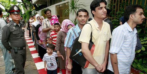A Thai police officer stands next to Pakistani refugees who walk in line to a waiting bus after they were released from the immigration detention center in Bangkok, Thailand Monday, June 6, 2011. - AP